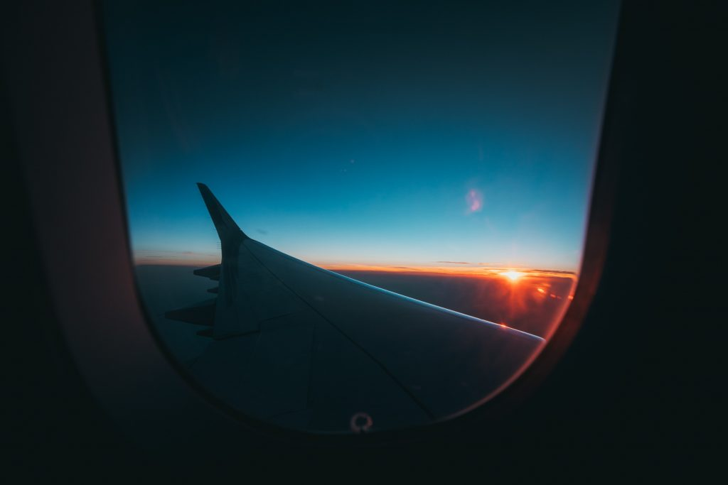 red eye flight tips for when you fly over night - view of the sunrise through a plane window